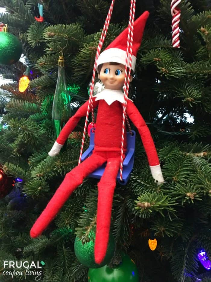 Are you following all of Frugal Coupon Living'sElfon the Shelf Ideas? See well over 100s of creative, funny, and original ideas for your Elf! Find Elf in a swing on the tree using theElves At Play Kit. #elfontheshelf #elf #elfontheshelfideas #funnyelf #elfideas #elfdoll