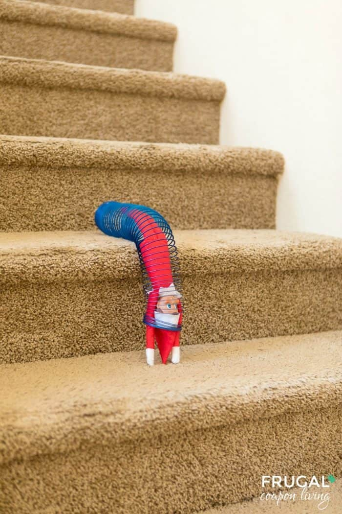 Elf in a Slinky, down the stairs, what fun!  | Elf on the Shelf Ideas | Free Elf Printables #FrugalCouponLiving #ElfontheShelf #ElfontheShelfIdeas #ElfIdeas #funnyelfideas #funnyelfontheshelf #elfprintables #freeelfprintables #printables #freeprintables